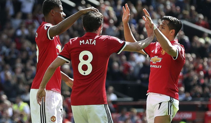 Manchester United's Marcus Rashford, left, celebrates with teammates Juan Mata, center, and Alexis Sanchez after scoring his side's first goal during their English Premier League soccer match against Watford at Old Trafford, Manchester, England, Sunday, May 13, 2018. (Martin Rickett/PA via AP)
