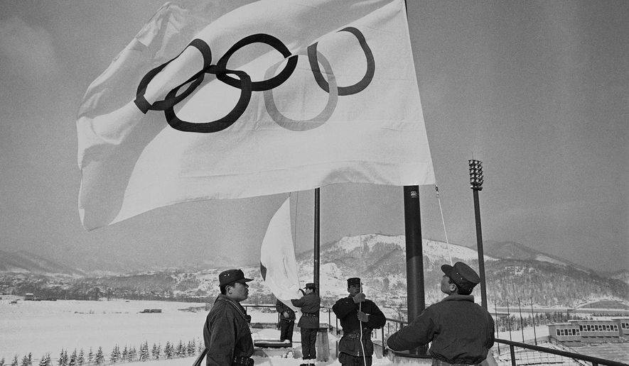 FILE - In this Jan. 23, 1972, file photo, members of Japan's self-defense ground forces raise Olympic Flags in Sapporo at Makomanai speed skating stadium in rehearsal of ceremony at official opening of Winter Olympic. Japanese officials are being vague about the city of Sapporo's effort to land the Winter Olympic Games.  City officials said mid-May 2018, that a bid for the 2030 Olympics seems more likely than pursuing 2026.  Sapporo is one of seven bidders in preliminary talks with the International Olympic Committee about 2026.  (AP Photo, File)