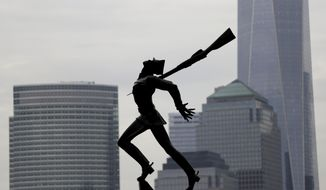 FILE - In this May 4, 2018, file photo, buildings in Lower Manhattan provide a backdrop to a statue dedicated to the victims of the Katyn massacre of 1940, in Jersey City, N.J. Jersey City Mayor Steve Fulop and local Polish groups announced late Saturday that they have reached an agreement on relocating the Katyn Memorial. Details on the deal will be announced during a news conference Monday, May 14. (AP Photo/Julio Cortez, File)