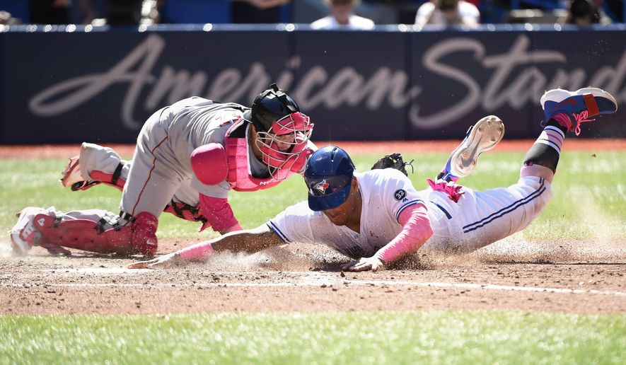 Toronto Blue Jays' Yangervis Solarte, foreground, is tagged out by Boston Red Sox catcher Christian Vazquez at home plate during seventh-inning baseball game action in Toronto, Sunday, May 13, 2018. (Nathan Denette/The Canadian Press via AP)