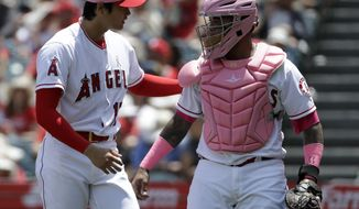 Los Angeles Angels starting pitcher Shohei Ohtani, left, of Japan, talks with catcher Martin Maldonado after the top of the first inning against the Minnesota Twins during a baseball game in Anaheim, Calif., Sunday, May 13, 2018.(AP Photo/Chris Carlson)
