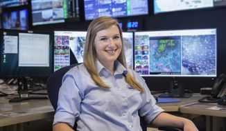 In this Friday, May 4, 2018, photo, Meteorologist Chelsea Kryston sits at the National Weather Service in Las Vegas. With all the technological advances in weather forecasting over the years, National Weather Service officials in Las Vegas and across the country still rely on a decades-old practice to fine tune their outlook _ twice-daily launching of weather balloons. (Benjamin Hager/Las Vegas Review-Journal via AP)