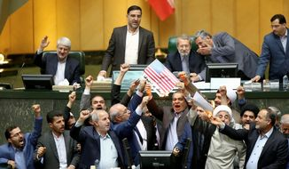 """Iranian lawmakers burn two pieces of papers representing the U.S. flag and the nuclear deal as they chant slogans against the U.S. at the parliament in Tehran, Iran, Wednesday, May 9, 2018. Iranian lawmakers have set a paper U.S. flag ablaze at parliament after President Donald Trump's nuclear deal pullout, shouting, """"Death to America!"""". President Donald Trump withdrew the U.S. from the deal on Tuesday and restored harsh sanctions against Iran. (AP Photo) (ASSOCIATED PRESS)"""