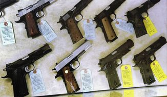 In this July 10, 2013, file photo, semi-automatic handguns are seen displayed for purchase at an arms supply store in Springfield, Ill. (AP Photo/Seth Perlman, File) **FILE**