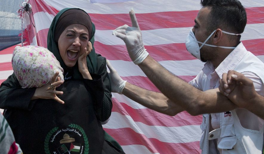 Palestinian woman reacts in a first aid tent during a protest near Beit Lahiya, Gaza Strip, Monday, May 14, 2018. Israeli soldiers shot and killed dozens of Palestinians during mass protests along the Gaza border on Monday. It was the deadliest day there since a devastating 2014 cross-border war and cast a pall over Israel's festive inauguration of the new U.S. Embassy in contested Jerusalem. (AP Photo/Dusan Vranic)