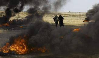 Palestinian women run for cover near the Gaza Strip's border with Israel, east of Khan Younis, in the Gaza Strip, Monday, May 14, 2018. Israeli fire has killed dozens of Palestinians during mass protests along the Gaza border, marking the deadliest day of violence since a devastating 2014 cross-border war and casting a pall over Israel's festive inauguration of the new U.S. Embassy in contested Jerusalem. (AP Photo/Adel Hana)