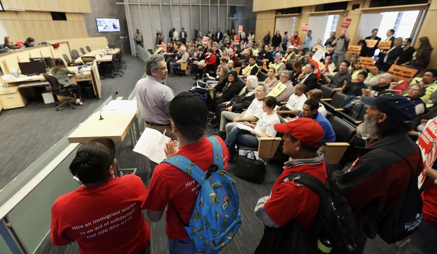 Members of Casa Latina, an immigrant worker rights organization, speak in favor of a controversial proposal to tax large businesses such as Amazon.com to fund efforts to combat homelessness, Wednesday, May 9, 2018, at a Seattle City Council committee meeting at City Hall in Seattle. (AP Photo/Ted S. Warren)