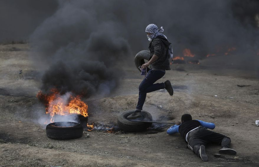 Palestinian protesters burn tires during a protest on the Gaza Strip's border with Israel, Monday, May 14, 2018. Thousands of Palestinians are protesting near Gaza's border with Israel, as Israel prepared for the festive inauguration of a new U.S. Embassy in contested Jerusalem. (AP Photo/Khalil Hamra)
