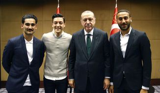 "In this photo taken on Sunday, May 13, 2018, Turkey's President Recep Tayyip Erdogan, right, poses for a photo with Turkish Premier League soccer players Ilkay Gundogan, left, Mesut Ozil, second left, and Cenk Tosun in London. Erdogan started a three-day visit to Britain on Sunday by praising the country as ""an ally and a strategic partner, but also a real friend."" (Presidential Press Service/Pool via AP)"