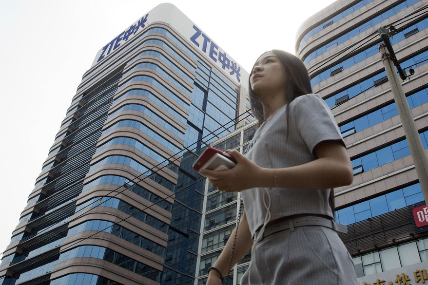 In this May 8, 2018, photo, a woman pass by a ZTE building in Beijing, China. President Donald Trump's weekend social media musings about China injected new uncertainty into the Washington's punishment of Chinese tech giant ZTE and planned trade talks between the two countries. (AP Photo/Ng Han Guan)