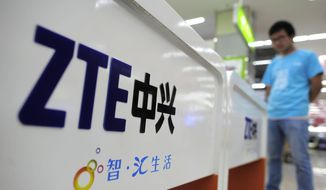 A salesperson stands at counters selling mobile phones produced by ZTE Corp. at an appliance store in Wuhan in central China's Hubei province on Oct. 8, 2012. (Chinatopix via AP) **FILE**