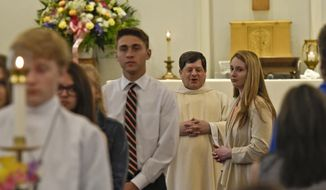 Rev. Alan Morris congratulates graduating students from Springdale, Saint Joseph and Fox Chapel Area high schools are honored during a senior recognition mass on Sunday, May 6, 2018 at Our Lady of Victory Parish in Springdale Township, Pa.  A review of local weekly church bulletins shows many parishes heavily promote programs catering to young children and older adults, playing on the longstanding belief that people tend to return to the church once they settle down and have children. (Jack Fordyce/Pittsburgh Tribune-Review via AP)