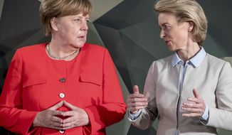 German Chancellor Angel Merkel, left, talks to defense minister Ursula von der Leyen to her visit to a Bundeswehr meeting in Berlin, Germany, Monday, May 14, 2018. ( Michael Kappeler/dpa via AP)