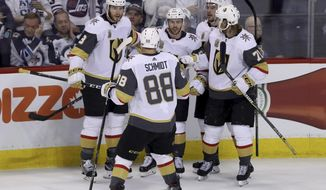 The Vegas Golden Knights' celebrate after Jonathan Marchessault (81) scored on Winnipeg Jets goaltender Connor Hellebuyck, not shown, during first period game 2 NHL Western Conference Finals hockey action in Winnipeg, Manitoba, Monday, May 14, 2018. (Trevor Hagan/The Canadian Press via AP)
