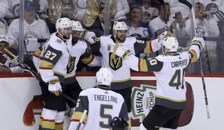 The Las Vegas Golden Knights celebrate after Tomas Tatar (90) scored on Winnipeg Jets goaltender Connor Hellebuyck (37) during first period game 2 NHL Western Conference Finals hockey action in Winnipeg, Manitoba, Monday, May 14, 2018. (Trevor Hagan/The Canadian Press via AP)