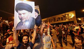 Followers of Shiite cleric Muqtada al-Sadr, seen in the posters, celebrate in Tahrir Square in Baghdad, Iraq, early Monday, May 14, 2018. Iraq's electoral commission announces influential Shiite cleric Muqtada al-Sadr is the current front-runner in national elections with official results in from just over half of the country's provinces. (AP Photo/Hadi Mizban)