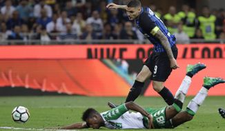 Inter Milan's Mauro Icardi, top, and Sassuolo's Claud Adjapong go for the ball during the Serie A soccer match between Inter Milan and Sassuolo at the San Siro stadium in Milan, Italy, Saturday, May 12, 2018. (AP Photo/Luca Bruno)