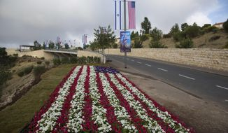 Flowers decorated as an American flag are seen on a road leading to the U.S. Embassy compound ahead the official opening in Jerusalem, Sunday, May 13, 2018. On Monday, the United States moves its embassy in Israel from Tel Aviv to Jerusalem, the holy city at the explosive core of the Israeli-Palestinian conflict and claimed by both sides as a capital. The inauguration comes five months after President Donald Trump recognized Jerusalem as Israel's capital. (AP Photo/Ariel Schalit)