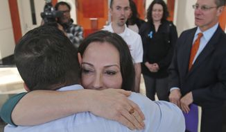 Terry Mitchell receives a hug from her husband Greg following a hearing, which is a key test of a law aimed at allowing people who say they were sexually abused to sue decades later, at the Utah Supreme Court Monday, May 14, 2018, in Salt Lake City, The Utah Supreme Court heard arguments in a lawsuit against a former federal judge accused of sexually assaulting a teenage witness when he was a prosecutor handling a white supremacist serial-killer trial. The suit was filed by Mitchell who says Richard W. Roberts, who went on to be a federal judge, abused her in Utah in 1981. (AP Photo/Rick Bowmer)