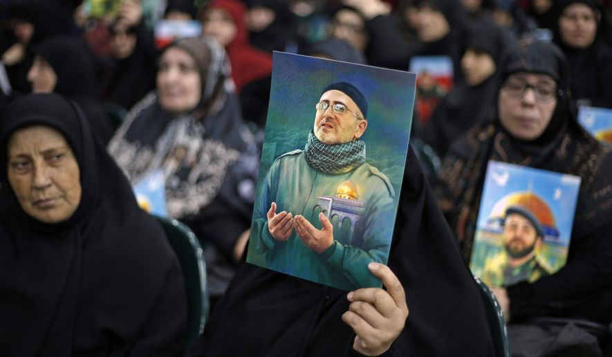 """Women hold pictures of Hezbollah slain top commander Mustafa Badreddine, who was killed in an explosion in Damascus, as they listen to Hezbollah leader Sheik Hassan Nasrallah, during a ceremony to mark the second anniversary of his death, in the southern suburbs of Beirut, Lebanon, Monday, May 14, 2018. Nasrallah said a barrage of rockets from Syria against Israeli forces in the occupied Golan Heights last week opens """"a new phase"""" in the conflict, warning that Israel proper could be the target next time. (AP Photo/Bilal Hussein)"""