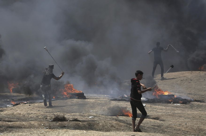 Palestinian protesters hurl stones at Israeli troops during a protest on the Gaza Strip's border with Israel, Monday, May 14, 2018. Thousands of Palestinians are protesting near Gaza's border with Israel, as Israel prepared for the festive inauguration of a new U.S. Embassy in contested Jerusalem. (AP Photo/Khalil Hamra)