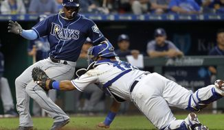 Tampa Bay Rays' Adeiny Hechavarria beats the tag by Kansas City Royals catcher Salvador Perez to score on a single hit by Matt Duffy during the sixth inning of a baseball game Monday, May 14, 2018, in Kansas City, Mo. (AP Photo/Charlie Riedel)