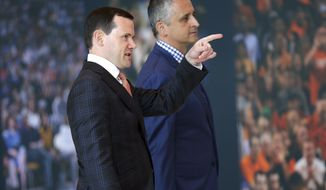 Phoenix Suns new head coach Igor Kokoskov, right, arrives with general manager Ryan McDonough to speak to the media Monday, May 14, 2018, in Phoenix. Kokoskov will oversee a vastly improved team after they compiled the worst record in the NBA last season. (AP Photo/Matt York)