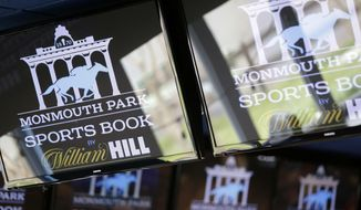 Signs for Monmouth Park are displayed in a bar at the racetrack in Oceanport, N.J., Monday, May 14, 2018. The Supreme Court on Monday gave its go-ahead for states to allow gambling on sports across the nation, striking down a federal law that barred betting on football, basketball, baseball and other sports in most states. (AP Photo/Seth Wenig)