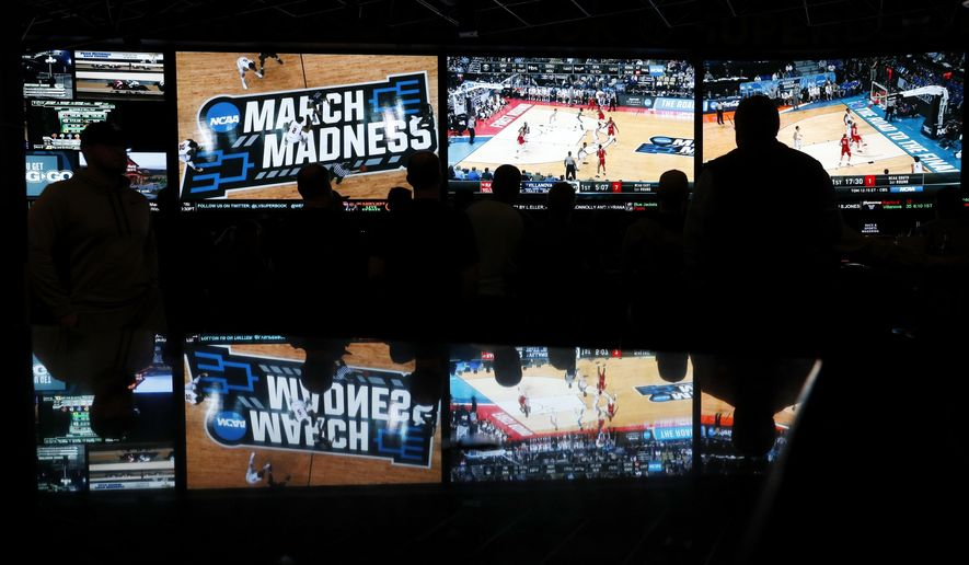 In this March 15, 2018 photo, people watch coverage of the first round of the NCAA college basketball tournament at the Westgate Superbook sports book in Las Vegas. The Supreme Court has struck down a federal law that bars gambling on football, basketball, baseball and other sports in most states, giving states the go-ahead to legalize betting on sports.   (AP Photo/John Locher)
