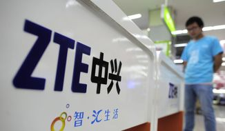 In this Oct. 8, 2012, file photo, a salesperson stands at counters selling mobile phones produced by ZTE Corp. at an appliance store in Wuhan in central China's Hubei province. (Chinatopix Via AP, File)
