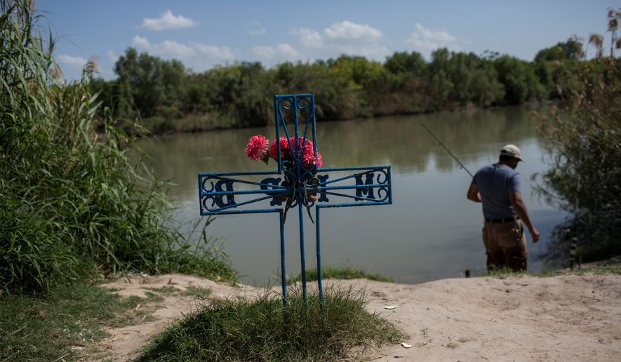 In this file photo dated Saturday, March 25, 2017, a man fishes in the river near to a cross in memory of a migrant who died trying to cross to the U.S., on the bank of the Rio Grande river in Nuevo Laredo, Tamaulipas state, Mexico, across the border from Laredo, Texas. (AP Photo/Rodrigo Abd, FILE)  **FILE**