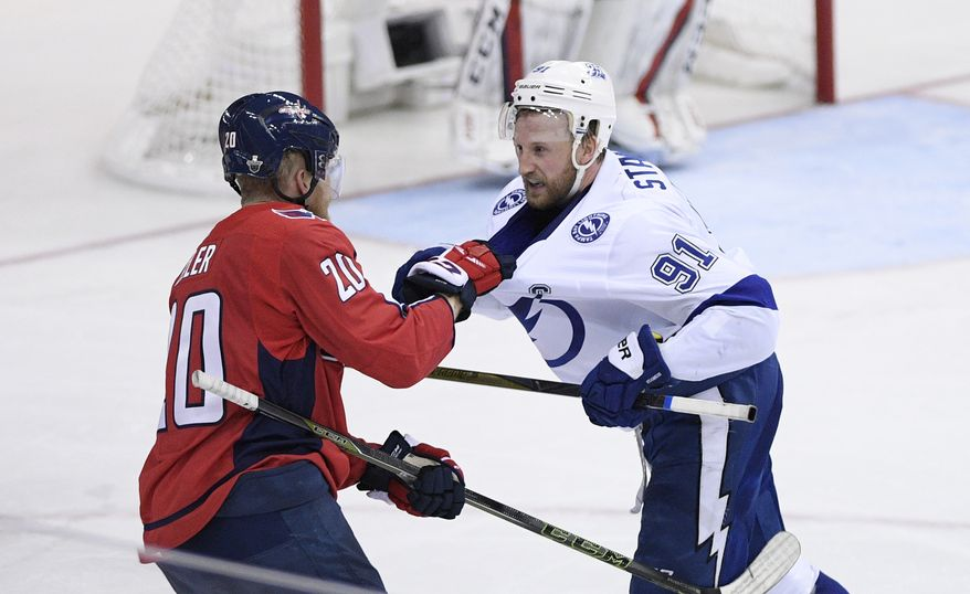 Washington Capitals center Lars Eller (20) pulls on the jersey of Tampa Bay Lightning center Steven Stamkos (91) during the third period of Game 3 of the NHL Eastern Conference finals hockey playoff series, Tuesday, May 15, 2018 in Washington. The Lightning won 4-2. (AP Photo/Nick Wass)