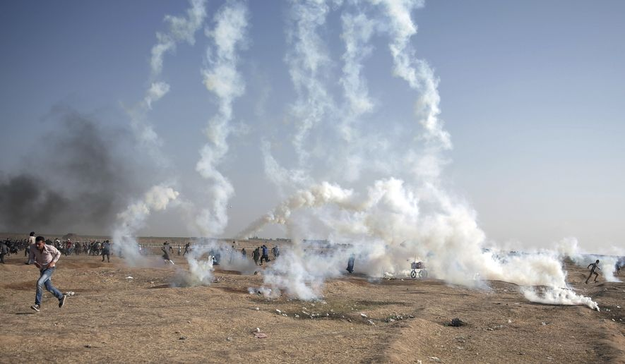Palestinian protesters run for cover from teargas fired by Israeli troops during a protest at the Gaza Strip's border with Israel, Tuesday, May 15, 2018. Israel faced a growing backlash Tuesday and new charges of using excessive force, a day after Israeli troops firing from across a border fence killed dozens of Palestinians and wounded more than 2,700 at a mass protest in Gaza. (AP Photo/Khalil Hamra)