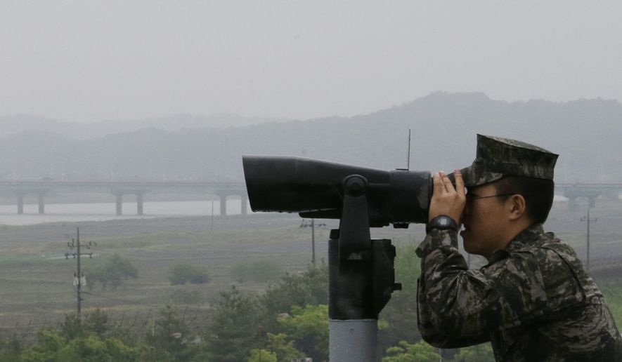 A South Korean marine force member looks toward North's side through binoculars at the Imjingak Pavilion in Paju near the border village of Panmunjom, South Korea, Wednesday, May 16, 2018. North Korea on Wednesday canceled a high-level meeting with South Korea and threatened to scrap a historic summit next month between U.S. President Donald Trump and North Korean leader Kim Jong Un over military exercises between Seoul and Washington that Pyongyang has long claimed are invasion rehearsals. (AP Photo/Ahn Young-joon)