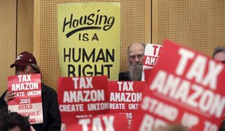 Members of the public look on at a Seattle City Council before the council voted to approve a tax on large businesses such as Amazon and Starbucks to fight homelessness, Monday, May 14, 2018, in Seattle. The council on Monday unanimously backed a compromise tax plan that will charge large businesses about $275 per full-time worker a year. It's lower than the $500-per-worker tax initially proposed. The tax would begin in 2019 and raise about $48 million a year to pay for affordable housing and homeless services. (AP Photo/Elaine Thompson)