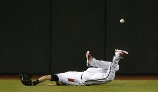 Arizona Diamondbacks center fielder A.J. Pollock lands awkwardly as he dives for a line drive hit by Milwaukee Brewers' Tyler Saladino, who ended up with an inside-the-park home run during the ninth inning of a baseball game Monday, May 14, 2018, in Phoenix. The Brewers defeated the Diamondbacks 7-2. (AP Photo/Ross D. Franklin)