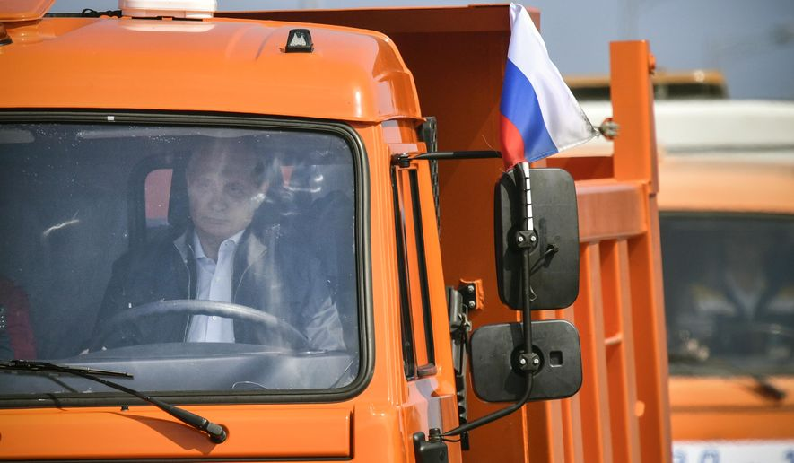 Russian President Vladimir Putin drives a truck to officially open the much-anticipated bridge linking Russia and the Crimean peninsula, during the opening ceremony near in Kerch, Crimea, Tuesday, May 15, 2018.  Putin has taken to the wheel of a truck to officially open the bridge linking Russia's south and the Crimean peninsula that Russia annexed from Ukraine in 2014. (Alexander Nemenov/Pool Photo via AP)