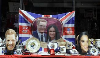 Merchandise is displayed for sale in a shop window in Windsor, England, Monday, May 14, 2018. Preparations are being made in the town ahead of the wedding of Britain's Prince Harry and Meghan Markle that will take place in Windsor on Saturday May 19. (AP Photo/Kirsty Wigglesworth)