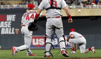 St. Louis Cardinals pitcher Luke Gregerson, left, makes an errant throw on a bunt attempt by Minnesota Twins' Byron Buxton which allowed a tie-breaking run to score in the seventh inning of a baseball game Tuesday, May 15, 2018, in Minneapolis. (AP Photo/Jim Mone)