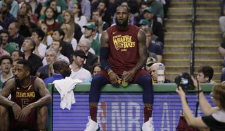 Cleveland Cavaliers forward LeBron James sits on the scorer's table during a timeout in the first half in Game 2 of the team's NBA basketball Eastern Conference finals against the Boston Celtics, Tuesday, May 15, 2018, in Boston. At left is teammate JR Smith. (AP Photo/Charles Krupa) **FILE**