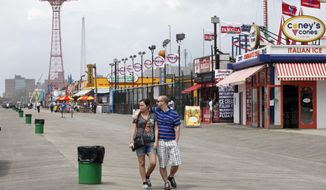 FILE - In this May 23, 2013 file photo, a couple walks on the boardwalk in Coney Island in the Brooklyn borough of New York. The New York City Landmarks Preservation Commission has designated Brooklyn's Coney Island boardwalk a Scenic Landmark.(AP Photo/Mark Lennihan, File)