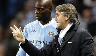 FILE - In this Wednesday Dec. 21, 2011 file photo Manchester City's manager Roberto Mancini, right, issues instructions to Italian stiker Mario Balotelli during the team's 3-0 win over Stoke in their English Premier League soccer match at The Etihad Stadium, Manchester, England.  Roberto Mancini has been confirmed as Italy's new coach, the Italian football federation made the announcement late Monday, May 15, 2018. (AP Photo/Jon Super, File)