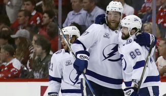 Tampa Bay Lightning center Brayden Point, left, defenseman Victor Hedman (77), from Sweden, and right wing Nikita Kucherov (86), from Russia, celebrate Kucherov's goal during the second period of Game 3 of the NHL Eastern Conference finals hockey playoff series against the Washington Capitals, Tuesday, May 15, 2018, in Washington. (AP Photo/Alex Brandon)