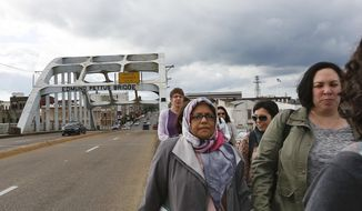 Members of the Sisterhood of Salaam Shalom group walk across the historic Edmund Pettus Bridge in Selma, Ala., on Tuesday, April, 24, 2018. The Sisterhood of Salaam Shalom brings together Jewish and Muslim women interested in learning about one another. (AP Photo/Brynn Anderson)