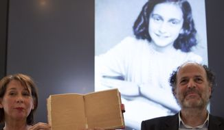 Teresien da Silva, left, and Ronald Leopold of the Anne Frank Foundation show a facsimile of Anne Frank's diary with two pages taped off during a press conference at the foundation's office in Amsterdam, Netherlands, Tuesday, May 15, 2018. Researchers have used digital photo editing techniques to uncover the text on two pages from Anne Frank's world famous diary that the teenage Jewish diarist had covered with brown masking paper, revealing risque jokes and an explanation of sex and prostitution. (AP Photo/Peter Dejong)