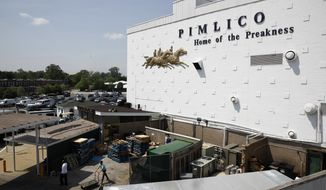 People walk outside of a building at Pimlico Race Course as preparations take place for the Preakness Stakes horse race, Tuesday, May 15, 2018, in Baltimore. Pimlico Race Course is getting all gussied up again this week, ready to host the Preakness on a day that will enable the 148-year-old track to survive another year. (AP Photo/Patrick Semansky)