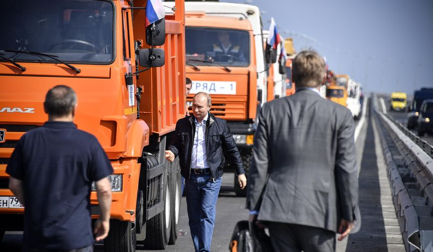Russian President Vladimir Putin walks after driving a truck to officially open the much-anticipated bridge linking Russia and the Crimean peninsula, during the opening ceremony near in Kerch, Crimea, Tuesday, May 15, 2018. Putin has taken to the wheel of a truck to officially open the bridge linking Russia's south and the Crimean peninsula that Russia annexed from Ukraine in 2014. (Alexander Nemenov/Pool Photo via AP) **FILE**