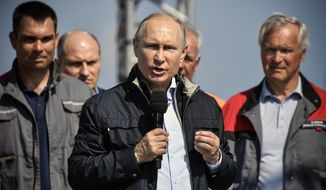Russian President Vladimir Putin speaks to a group of workers after driving to officially open the much-anticipated bridge linking Russia and the Crimean peninsula the opening ceremony near in Kerch, Crimea, Tuesday, May 15, 2018. Putin has taken the wheel of a truck to officially open the much-anticipated bridge linking Russia's south and the Crimean peninsula that Russia annexed from Ukraine in 2014. (Alexander Nemenov/Pool Photo via AP)