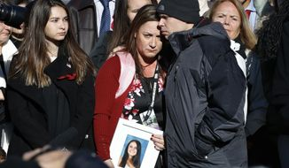 In a March 23, 2018, file photo, Lori Alhadeff, center, is comforted by her husband Ilan Alhadeff, as she holds a photograph of their daughter, Alyssa Alhadeff, 14, who was killed in the shootings at Marjory Stoneman Douglas High School, while they attend a news conference on gun violence, on Capitol Hill in Washington. Lori Alhadeff announced her candidacy Tuesday, May 15, 2018, for a seat on the school board in the district that includes the city of Parkland, where Stoneman Douglas is located. (AP Photo/Jacquelyn Martin, File)