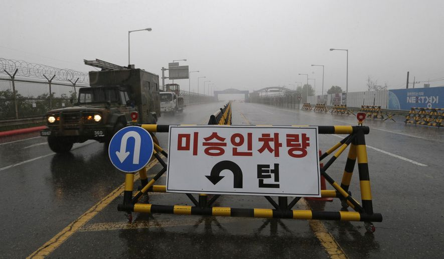 """A South Korean military vehicle crosses Unification Bridge, which leads to the demilitarized zone, near the border village of Panmunjom in Paju, South Korea, Wednesday, May 16, 2018. North Korea on Wednesday canceled a high-level meeting with South Korea and threatened to scrap a historic summit next month between U.S. President Donald Trump and North Korean leader Kim Jong Un over military exercises between Seoul and Washington that Pyongyang has long claimed are invasion rehearsals. The barricade reads: """"Vehicles disapproved."""" (AP Photo/Ahn Young-joon)"""
